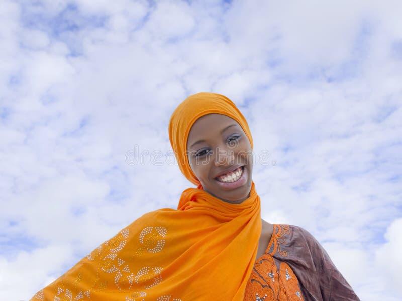 Belleza joven del Afro que lleva un pañuelo tradicional en la calle fotografía de archivo