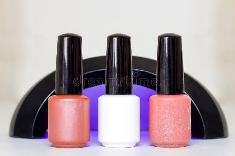 Belleza, moda y clavo Art Concept Manicure el esmalte de uñas beige blanco rosado ultravioleta de la lámpara de las herramientas  fotos de archivo libres de regalías