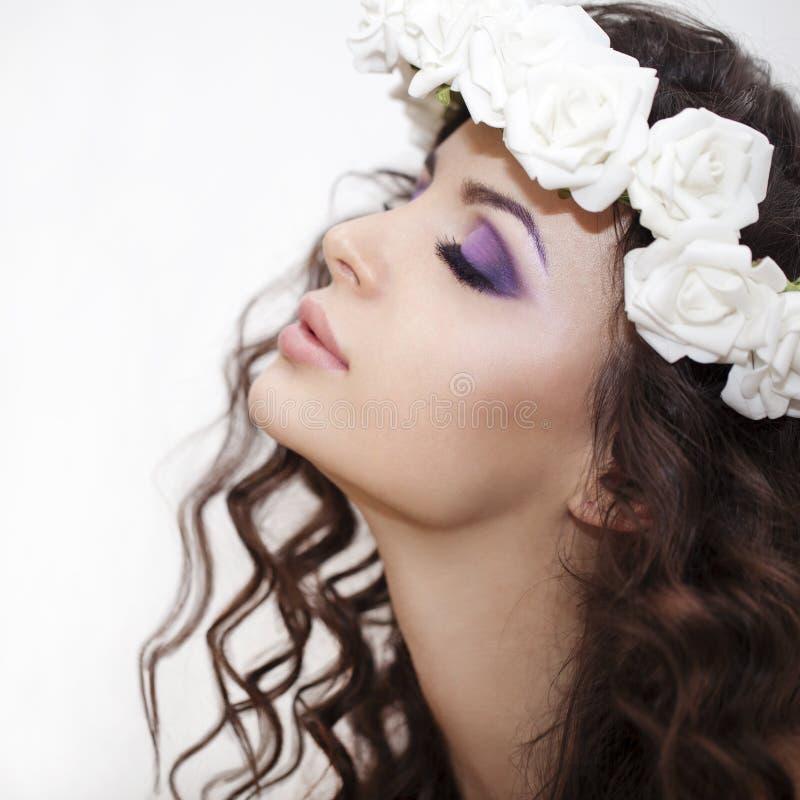 Belleza - morenita lujosa de la mujer joven con los pelos rizados largos sobre el fondo blanco fotos de archivo libres de regalías