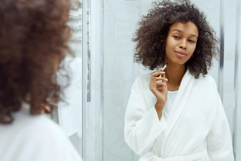 Belleza. Mujer sonriente con cepillo de maquillaje en el baño fotos de archivo