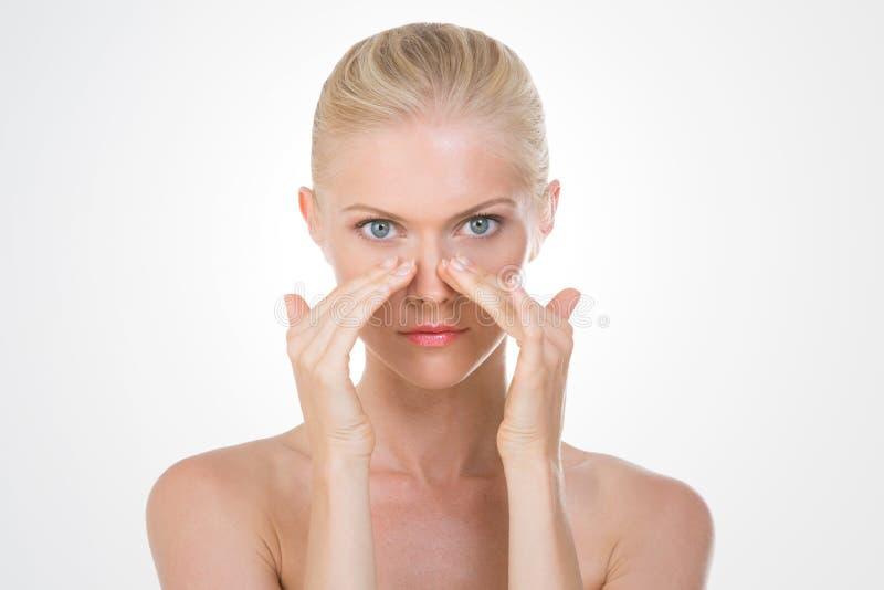 Belleza nórdica que aplica la crema en su nariz fotos de archivo