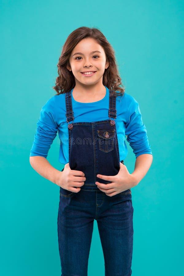 Belleza pura Niña con el pelo largo Cara linda feliz del niño con el soporte adorable del pelo rizado sobre fondo azul belleza fotos de archivo