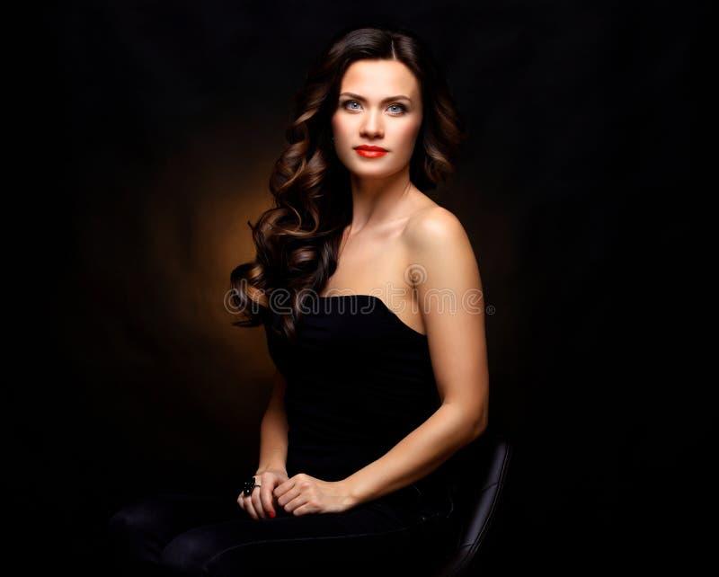 Belleza Woman modelo con el pelo ondulado largo de Brown Pelo sano y maquillaje profesional hermoso Labios rojos y ojos ahumados imagen de archivo libre de regalías