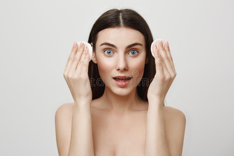 Belleza y concepto cosmetological del procedimiento Retrato de la mujer expresiva apuesta que sostiene los cojines de algodón en  foto de archivo libre de regalías