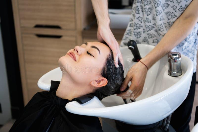 Belleza y concepto de la gente - mujer joven feliz con la cabeza que se lava del peluquero en el salón de pelo imágenes de archivo libres de regalías