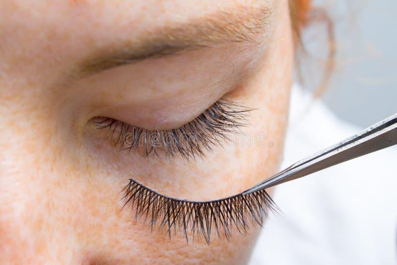 Belleza y concepto de la moda - procedimientos de la extensión de la pestaña La muchacha pelirroja del ojo cerrado con las pecas  imagenes de archivo