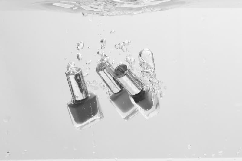 Belleza y concepto del cuidado Botellas del esmalte de uñas debajo del agua imagenes de archivo