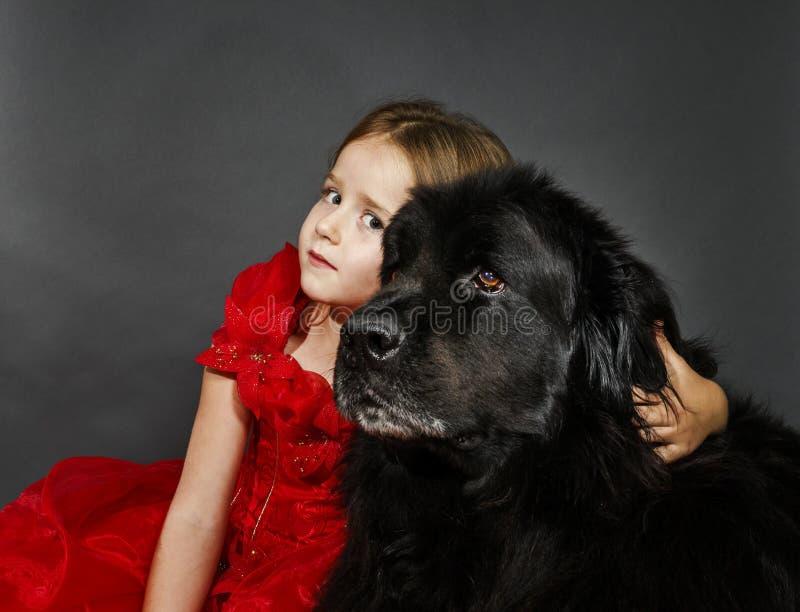 Belleza y la muchacha de la bestia con el agua-perro negro grande fotografía de archivo libre de regalías