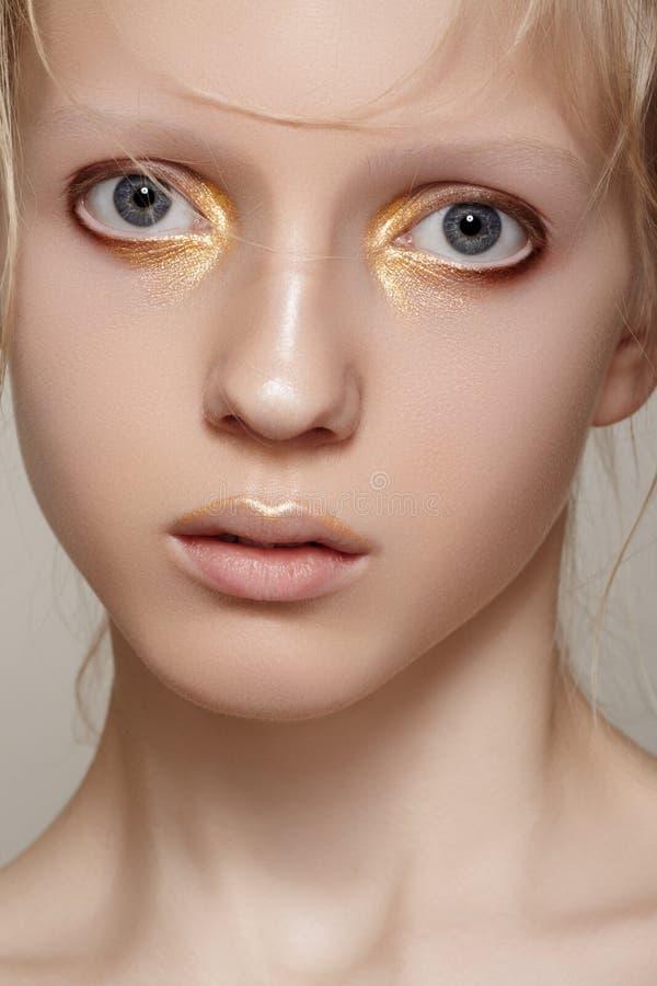 Belleza y moda. Cara modelo con maquillaje brillante del oro del día de fiesta, piel limpia de la muchacha imagen de archivo