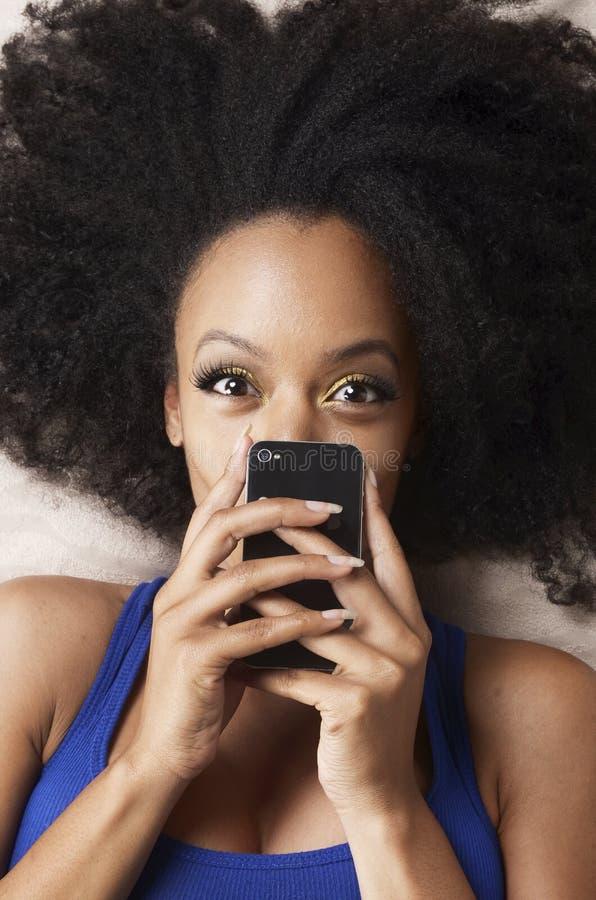 Bellezza afroamericana felice ed il suo telefono cellulare immagini stock