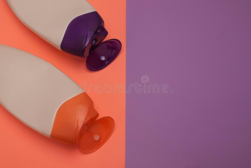 Bellezza, bottiglie decorative dei cosmetici Pesca e fondo porpora di colori, disposizione piana, vista superiore, stile minimali fotografia stock