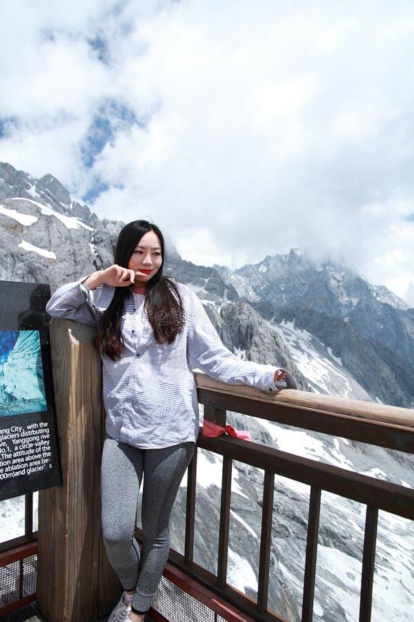 Bellezza cinese spensierata sulla montagna della neve del drago della giada del Yunnan immagine stock