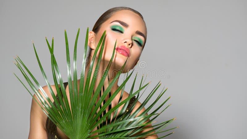 Bellezza con foglie di palma verde naturale Ritratto, modella con trucco perfetto, occhi verdi fotografia stock libera da diritti