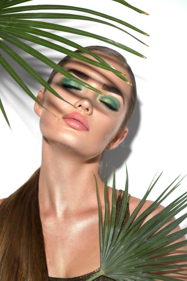 Bellezza con foglie di palma verde naturale Ritratto, modella con trucco perfetto, occhi verdi fotografia stock