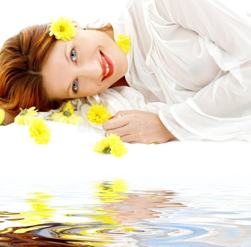 Bellezza con i fiori gialli sulla sabbia bianca fotografia stock