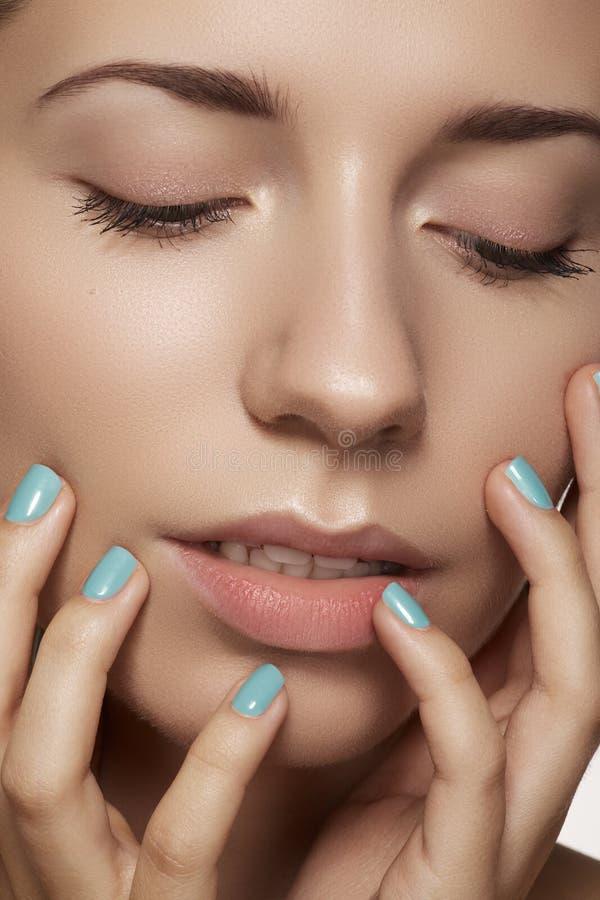 Bellezza del primo piano. Fronte di modello con trucco naturale & il manicure luminoso fotografia stock