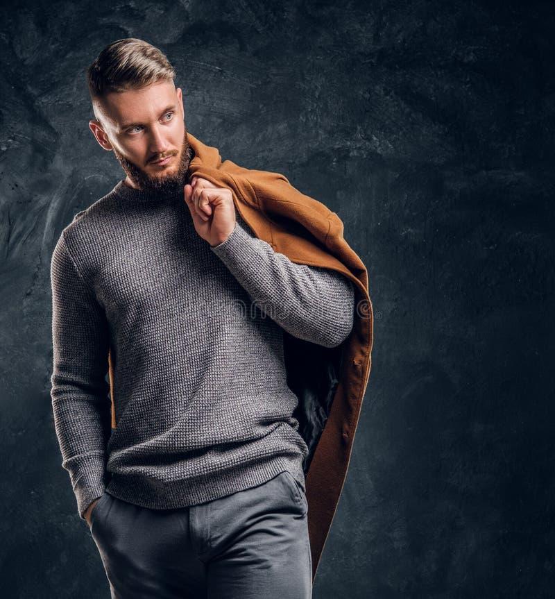Bellezza del ` s degli uomini, modo stagionale Ritratto di un maschio alla moda che tiene il suo cappotto di demi-stagione Foto d immagine stock