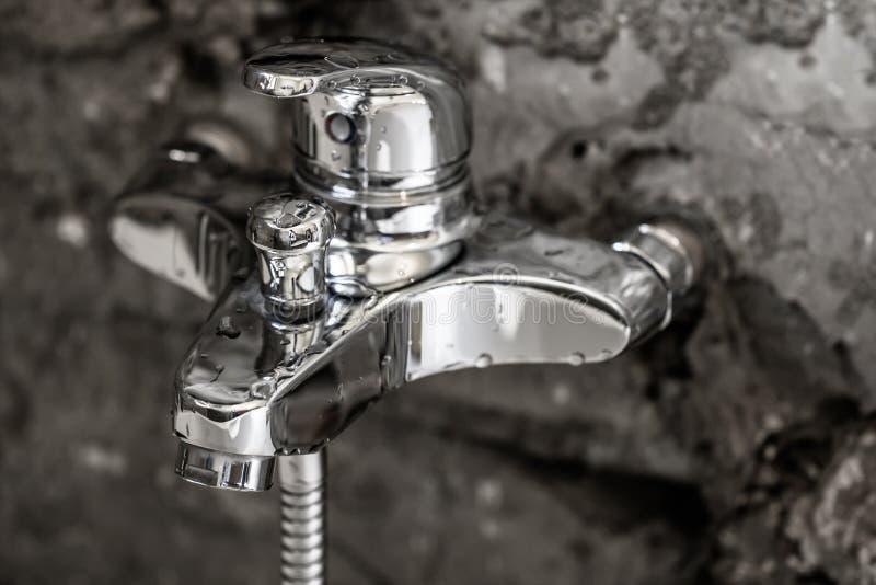 Bellezza della superficie brillante del cromo del metallo su un rubinetto del bagno con wate fotografia stock