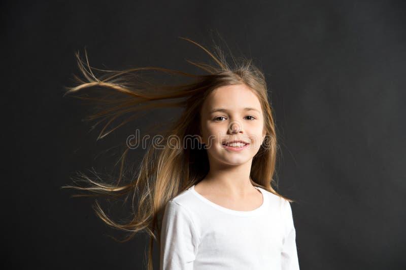 Bellezza naturale Volo lungo dei capelli del bambino della ragazza in aria, fondo nero Bambino con bei capelli sani naturali rapi fotografia stock libera da diritti
