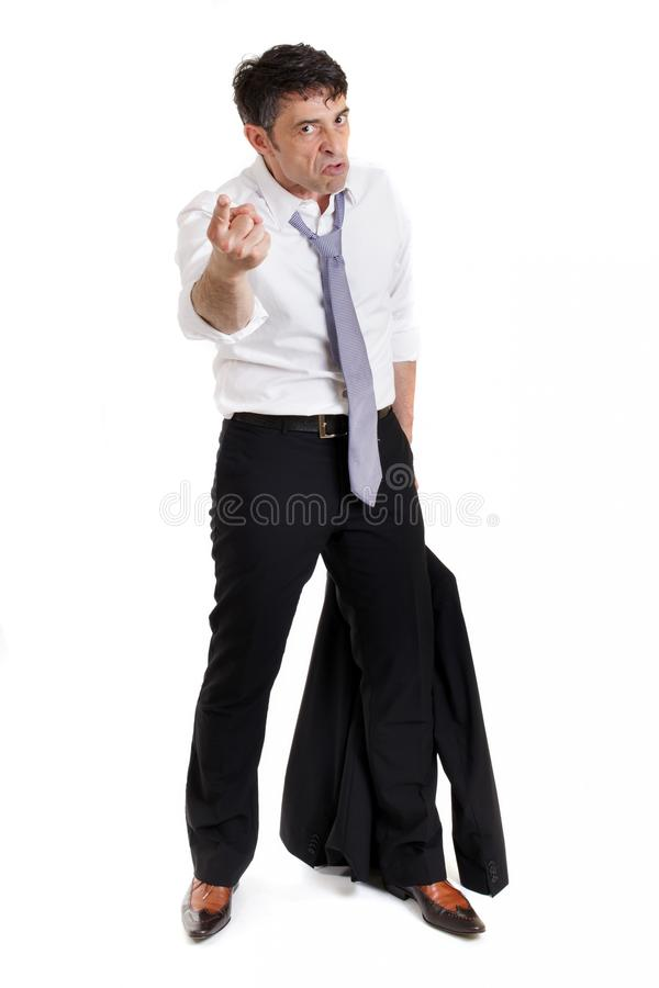 Belligerent businessman pointing. A threatening finger at the camera in anger with a ferocious expression, full length isolated on white stock image