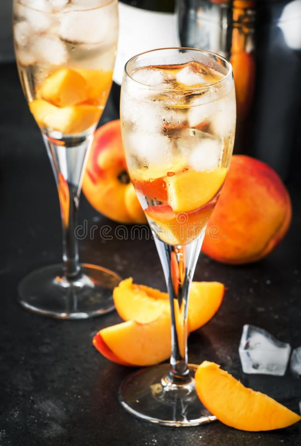 Bellini, alcoholic cocktail with sparkling wine, sugar syrup, lemon juice, peach and ice, gray table background, copy space royalty free stock images