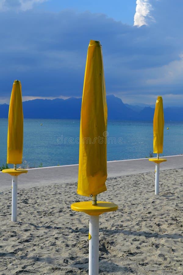 Bellissima costa del lago Garda con ombrelli gialli, Italia fotografia stock libera da diritti