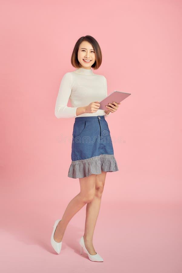 Bellissima donna asiatica che tiene in mano un libro e legge su sfondo rosa Lunghezza intera fotografie stock libere da diritti