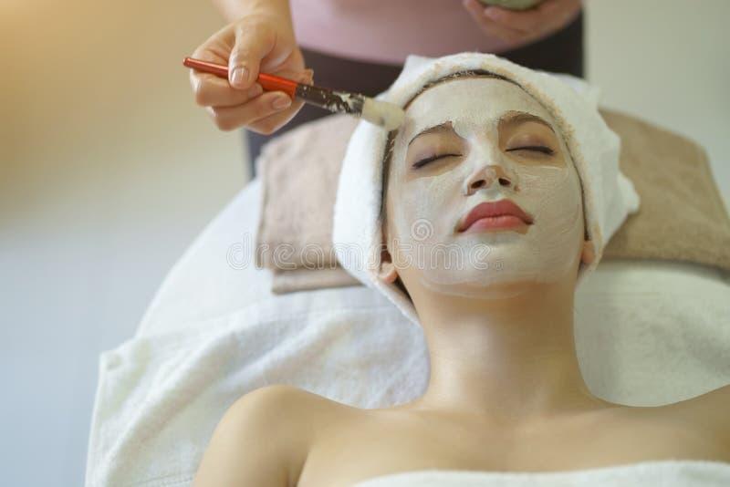 Bellissima donna caucasica con maschera, sdraiata sulla terrazza Trattamento del volto nella salone di Spa immagini stock