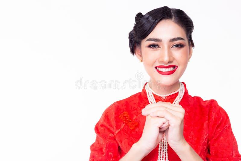 Bellissima donna cinese che saluta qualcuno in cinese capodanno Una donna asiatica benedice, sperando di ottenere prosperità fotografia stock libera da diritti