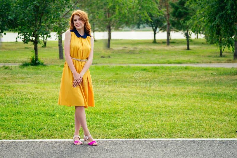 Bellissima giovane donna scozzese di zenzero con un vestito giallo e scarpe di tacchi alti eleganti nel parco estivo concetto di immagini stock