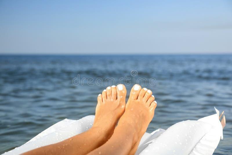 Bellissima giovane donna su materassi gonfiabili in mare Spazio per il testo immagini stock libere da diritti