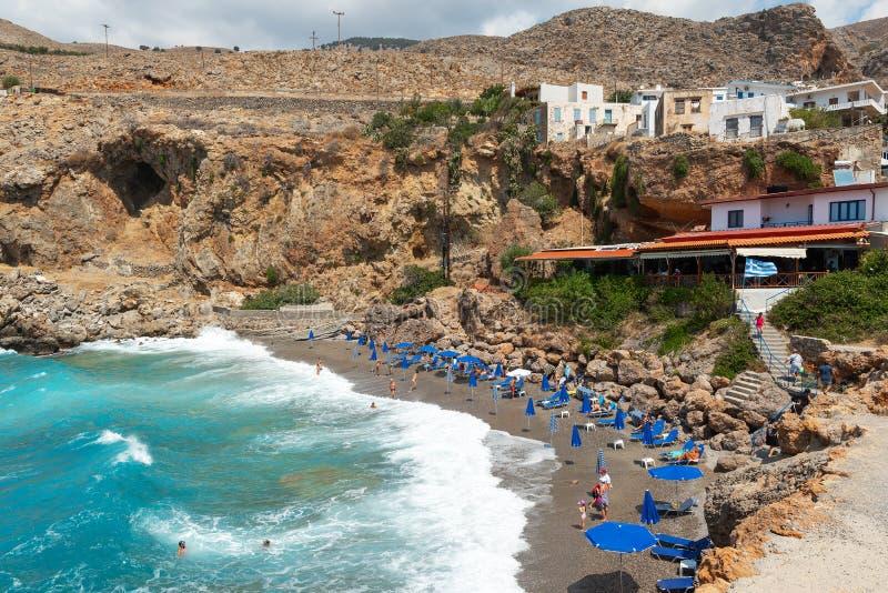 Bellissima laguna blu con ombrelli sulla spiaggia di Sandy, Chora Sfakion, città di Creta immagini stock