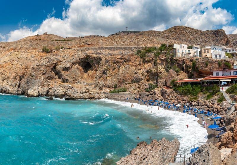 Bellissima laguna blu con ombrelli sulla spiaggia di Sandy, Chora Sfakion, città di Creta fotografia stock libera da diritti