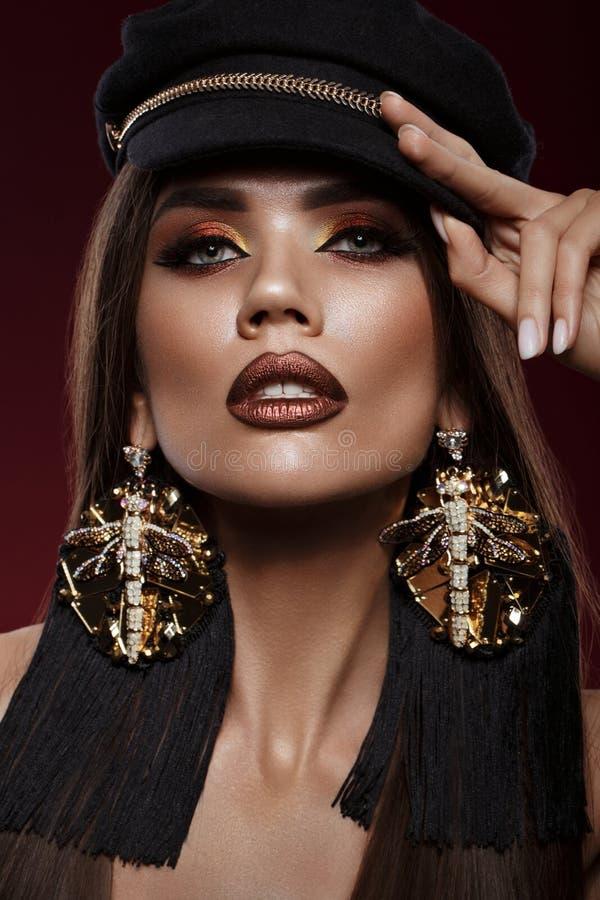 Bellissima ragazza brunetta con riccioli, trucco brillante e accessori di design Il volto di bellezza fotografia stock