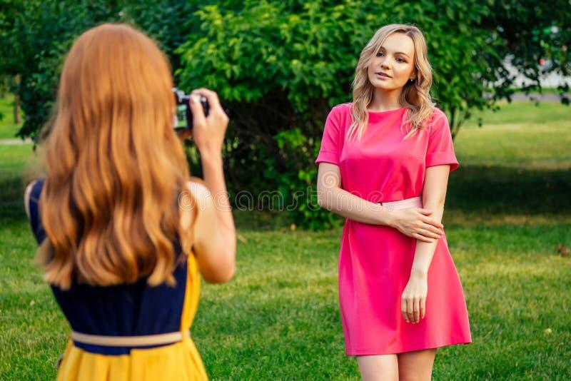 Bellissima ragazza rossa con un vestito giallo e una bionda europea in abito rosa fotografata immagine stock libera da diritti