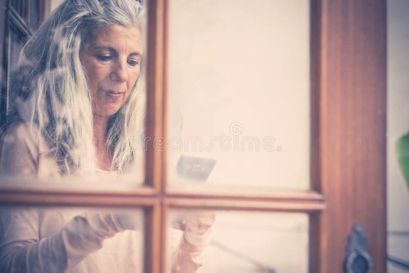 Bellissimo ritratto vintage vecchio stile di una donna anziana alternativa che scrive e legge un apparecchio da cellulare a casa, immagini stock libere da diritti