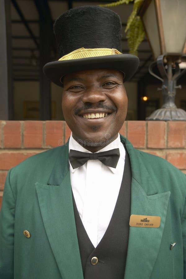 Bellman ono uśmiecha się przed historycznym Norfolk hotelem w Nairobia, Kenja, Afryka zdjęcie stock