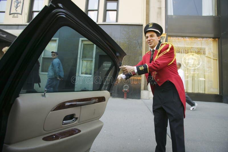 Bellman w czerwonej kurtce otwiera limo drzwi przed Helmsley parka pasa ruchu hotelem na central park Na zachód, w Manhattan, Mia obrazy stock