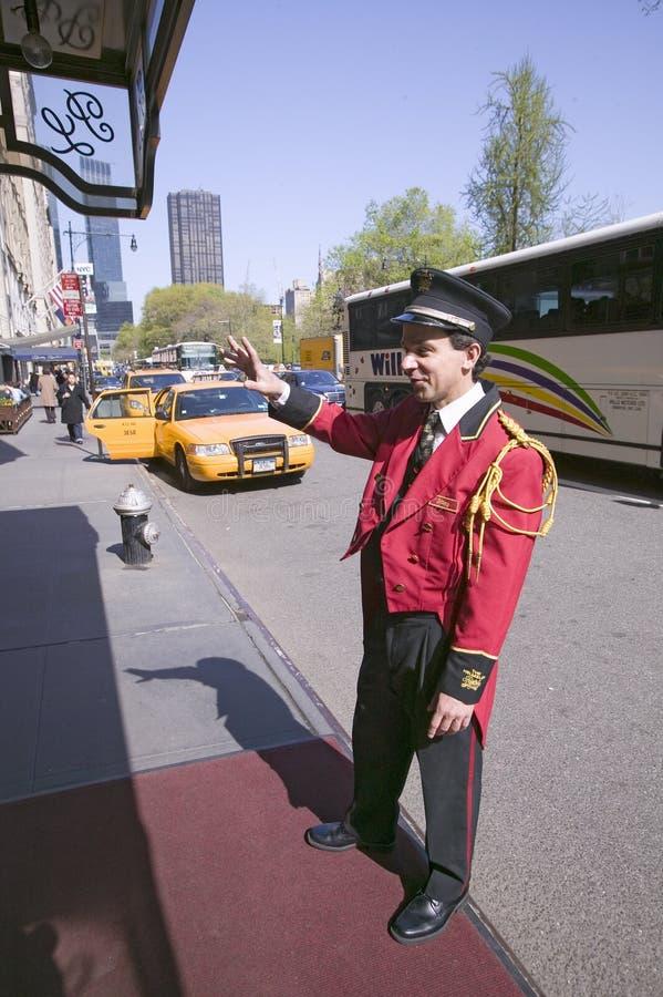 Bellman w czerwonych kurtek wezwaniach dla taksówki przed Helmsley parka pasa ruchu hotelem na central park Zachodni, w Manhattan zdjęcie stock