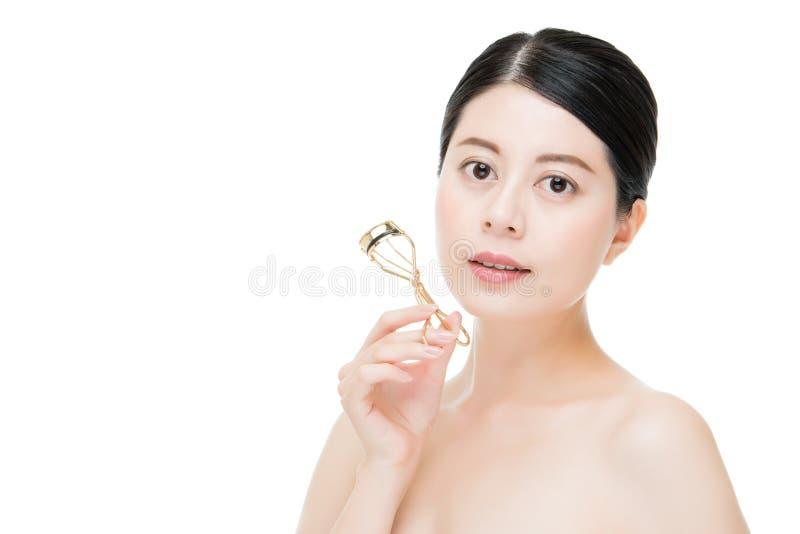 Bello accessorio di trucco del bigodino del ciglio della tenuta della ragazza di modo immagine stock libera da diritti