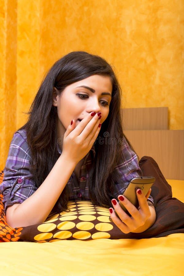 Bello adolescente che esamina il suo Smart Phone con i asthonis fotografia stock libera da diritti
