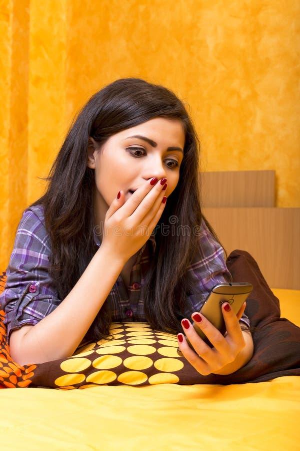 Bello adolescente che esamina il suo Smart Phone con i asthonis immagine stock libera da diritti