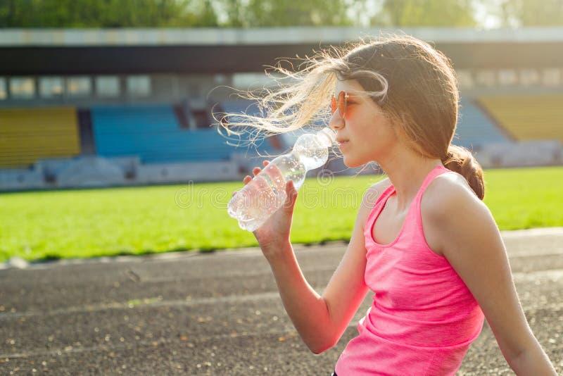 Bello adolescente che riposa dopo l'allenamento allo stadio, acqua potabile fotografia stock libera da diritti