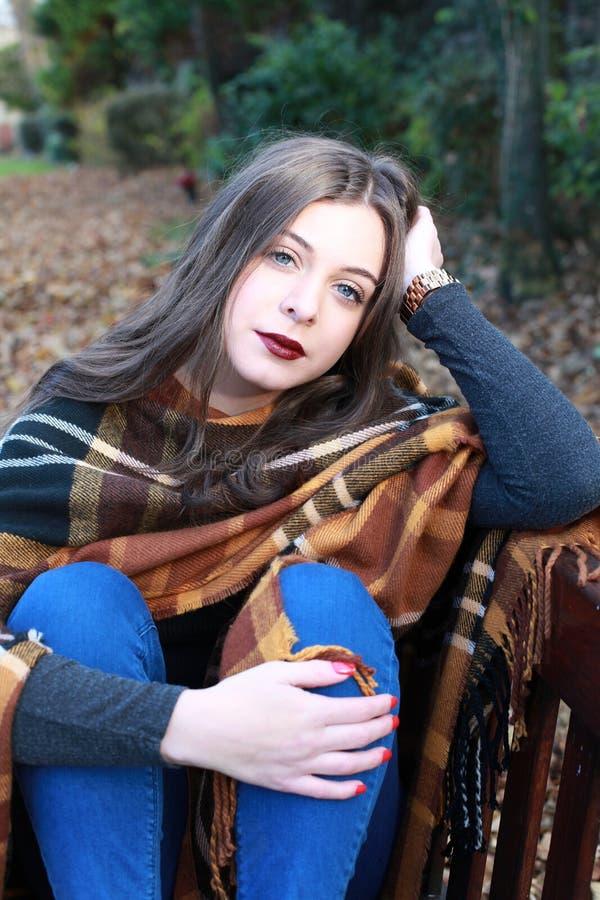 Bello adolescente che si siede su un banco di parco in autunno fotografia stock libera da diritti