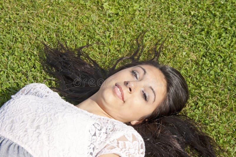 Bello adolescente che si trova sull'erba immagini stock libere da diritti