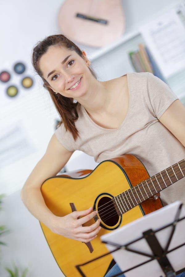 Bello adolescente della ragazza in camicia e jeans lacerati che giocano chitarra immagine stock