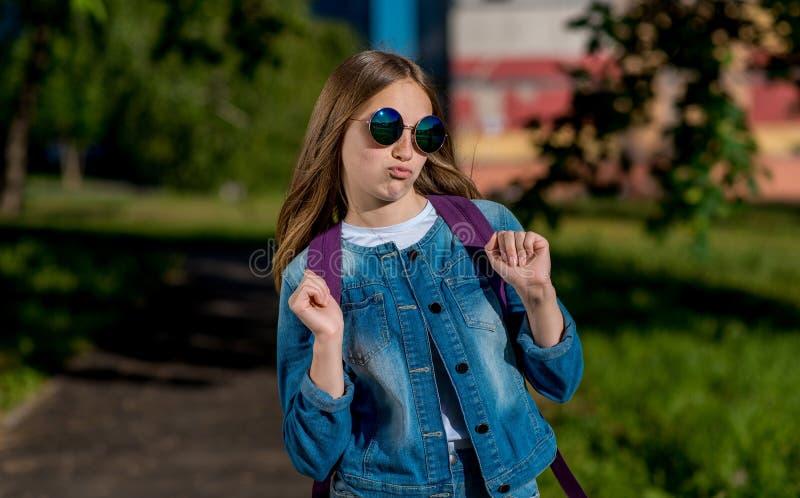 Bello adolescente della ragazza della scolara, di estate in parco sulla natura, sugli occhiali da sole d'uso dietro lo zaino ed i fotografie stock libere da diritti