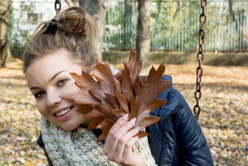 Bello adolescente sorridente con le foglie della quercia marrone fotografie stock libere da diritti