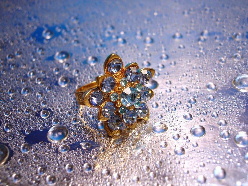 Bello anello blu su priorità bassa d'argento con goccia di acqua fotografie stock