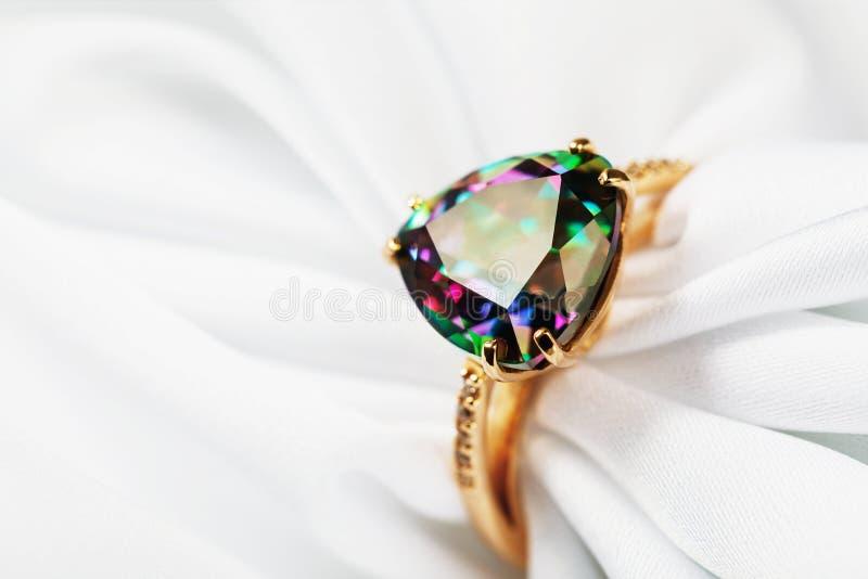 Bello anello di oro ornato con una grande gemma, iridescente nei colori differenti su un tessuto di seta bianco immagine stock